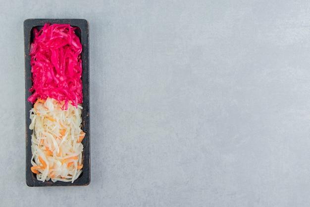 Grünes und rotes sauerkraut auf dem tablett auf der marmoroberfläche