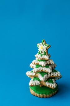 Grünes weihnachtsbaum-lebkuchenplätzchen auf blauer szene
