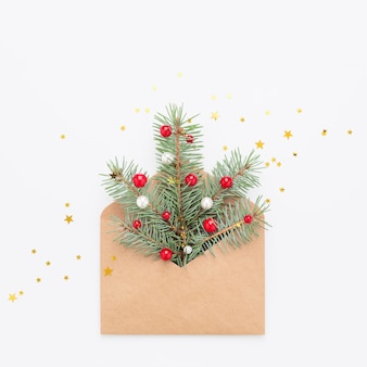 Grünes weihnachtsbaumsymbol im bastelpapierumschlag, konfetti auf weißem kopierraumhintergrund.