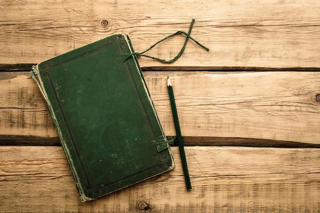 Grünes weinleseheft für notizen auf einem hölzernen hintergrund. speicherplatz kopieren. hochwertiges foto