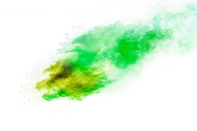 Grüngelber staub spritzt. explosionswolke des grünen gelben farbpulvers auf weißem hintergrund.