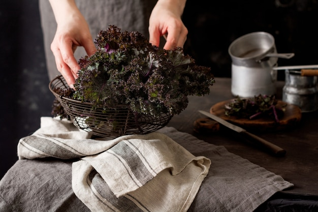 Grünkohl hinterlässt frische grüne lockige und weibliche hände in einem vintage-metallkorb auf einer alten holzoberfläche