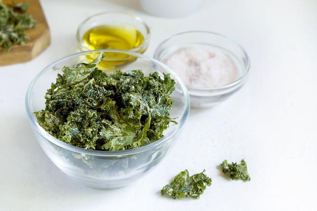 Grünkohlchips in der glasschale auf weißem hintergrund
