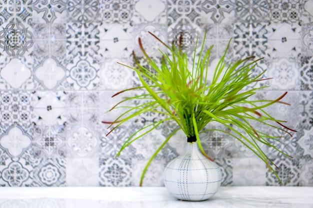 Grünpflanze im kleinen dekorativen weißen vase