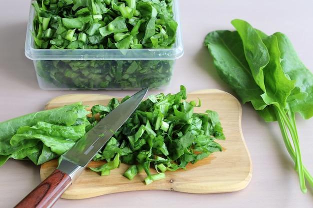 Grüns an bord mit messer und frischen blättern geschnitten