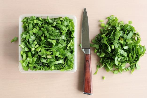 Grüns in scheiben geschnitten und messer auf dem tisch, vitamine für vegetarier, in flacher lage