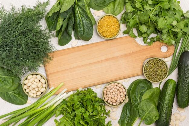 Grüns und getreide auf dem tisch. schneidebrett in der mitte. weißer hintergrund. flach legen