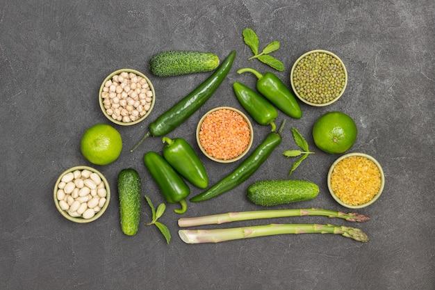 Grütze und grünes gemüse auf dem tisch. schwarzer hintergrund. flach legen