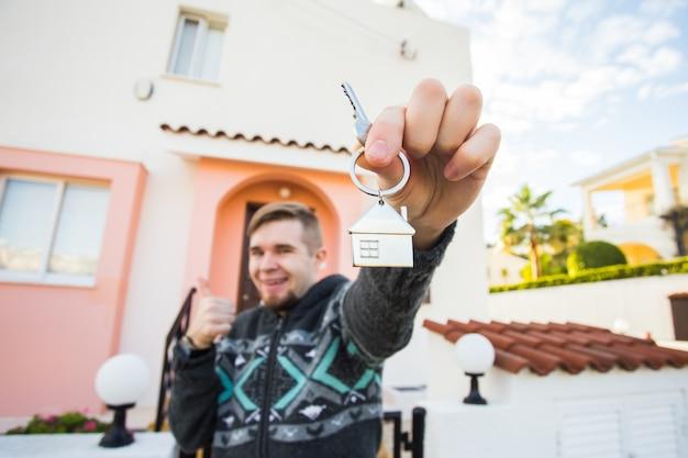 Grundbesitz neues zuhause und menschen konzept fröhlicher junger mann mit hausschlüssel