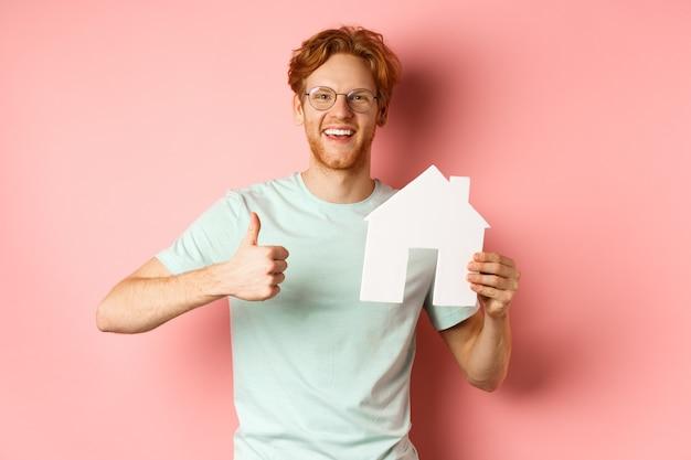 Grundeigentum. fröhlicher mann in brille und t-shirt, der makleragentur empfiehlt, papierausschnitt und daumen hoch zeigend, über rosa hintergrund stehend.