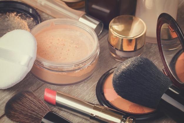 Grundlegende make-up-produkte auf dem tisch - grundierung, puder und lippenstift, retro getönt