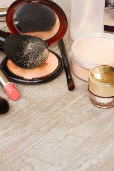 Grundlegende make-up-produkte - grundierung, puder und lippenstift auf holzhintergrund mit kopierraum