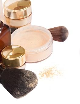 Grundlegende make-up-produkte - grundierung, pudernahaufnahme lokalisiert auf weißem hintergrund