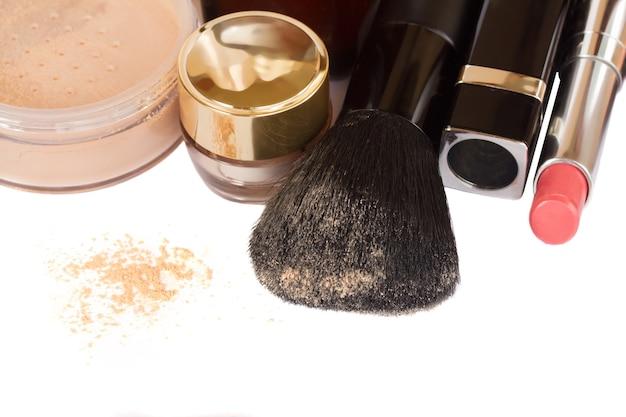 Grundlegende make-up-produkte mit bürsten- und lippenstiftrand isoliert auf weißem hintergrund