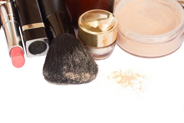 Grundlegende make-up-produkte mit gebürstetem rand lokalisiert auf weißem hintergrund