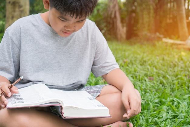Grundlegendes sitzen des asiatischen studentenjungen, das seine hausarbeit für das lernen der studie liest und tut