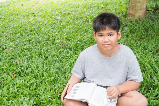 Grundlegendes sitzen des asiatischen studentenjungen, das seine hausarbeit liest und tut
