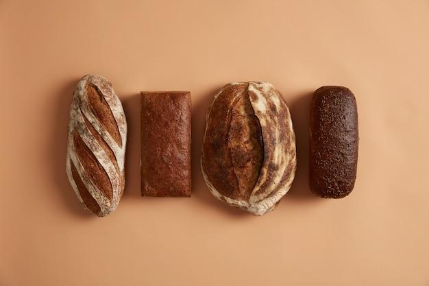 Grundnahrungsmittel und gesundes ernährungskonzept. vier arten von brot lokalisiert auf braunem hintergrund. weizen, roggen, dinkelbrot, angereichert mit vitaminen und mineralien aus bio-mehl, hat gesundheitliche vorteile