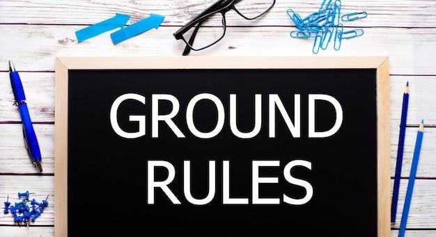 Grundregeln auf einer schwarzen notiztafel neben blauen büroklammern, bleistiften und einem stift.