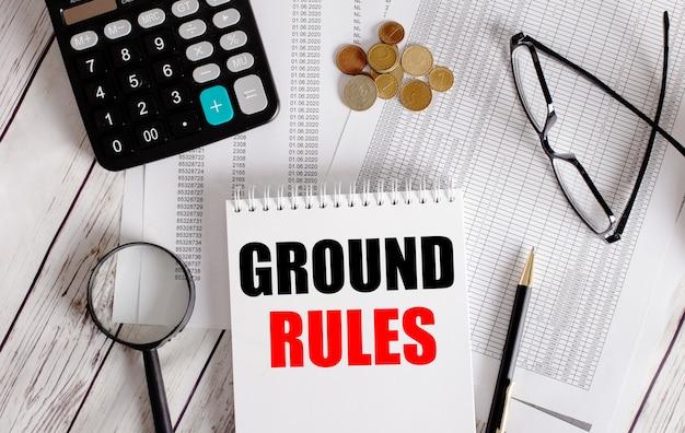 Grundregeln in einem weißen notizblock in der nähe eines taschenrechners, bargeld, brille, lupe und stift geschrieben. unternehmenskonzept