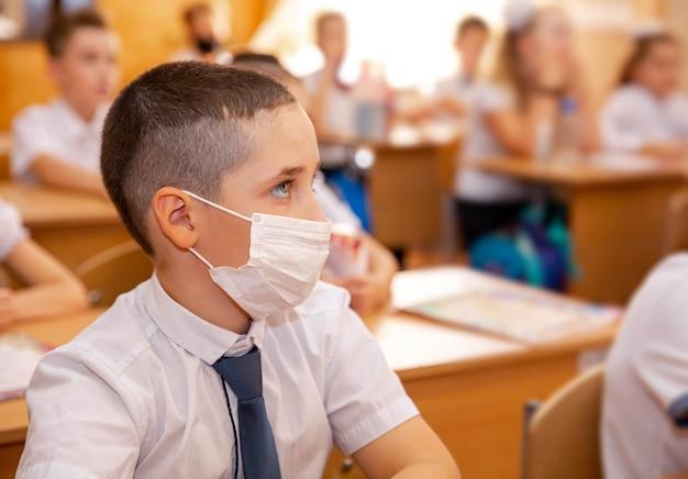 Grundschüler, der schularbeiten an schreibtischen im klassenzimmer erledigt