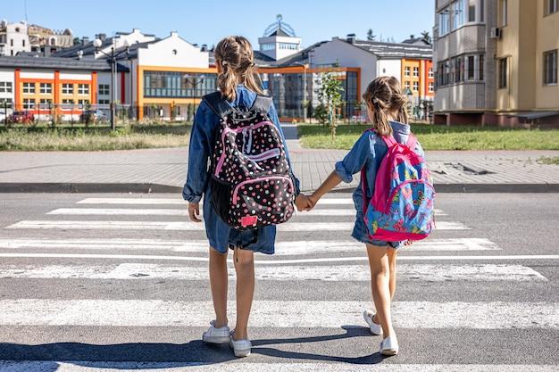 Grundschüler gehen zur schule, händchen haltend, erster schultag, zurück zur schule.