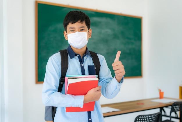 Grundschüler mit rucksack und büchern, die eine gesichtsmaske tragen