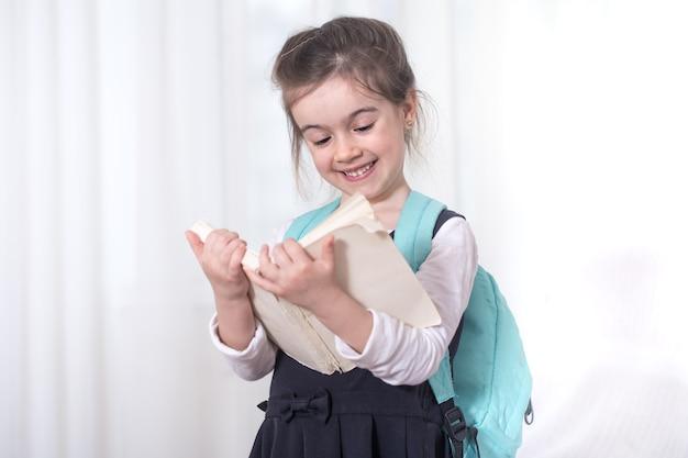 Grundschülerin mit einem rucksack auf den schultern, der ein buch auf hellem hintergrund liest. das konzept der bildung und der grundschule