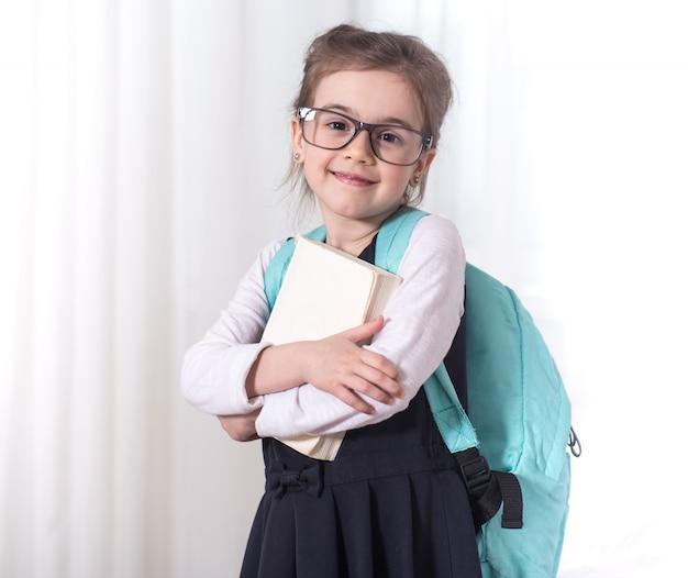 Grundschülerin mit rucksack und buch