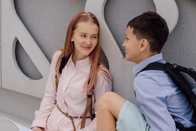 Grundschulbildung, schule, das konzept der freundschaft - zwei studentenjunge und ein mädchen im teenageralter mit rucksäcken sitzen und unterhalten sich nach der schule