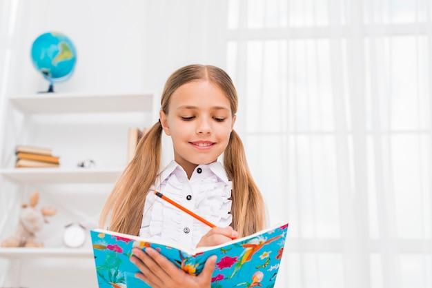 Grundschulemädchen, das hausarbeit tuend steht