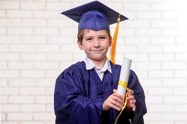 Grundschuljunge in tasse und kleid posiert mit diplom.