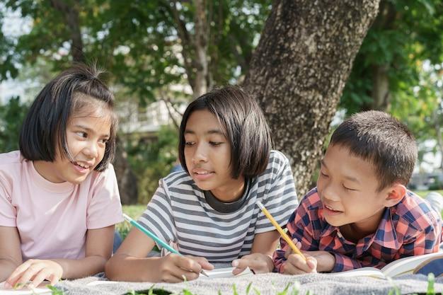 Grundschulkinder der asian group schreiben ein notizbuch mit einem bleistift und lernen gemeinsam im park
