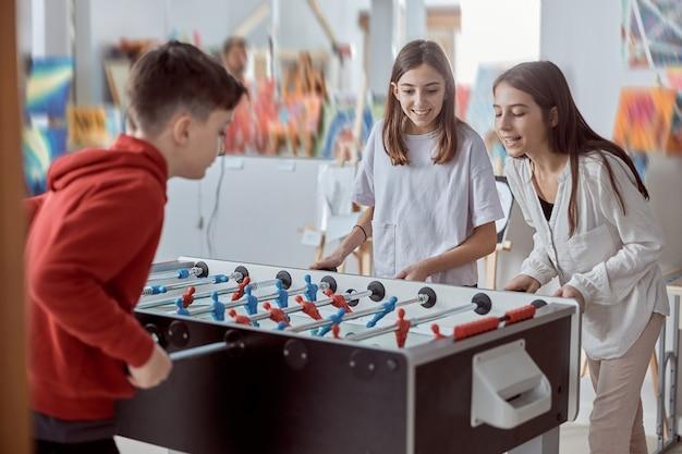 Grundschulkinder in einem klassenzimmer, das tischfußball spielt. spaß in der pause in der schule.