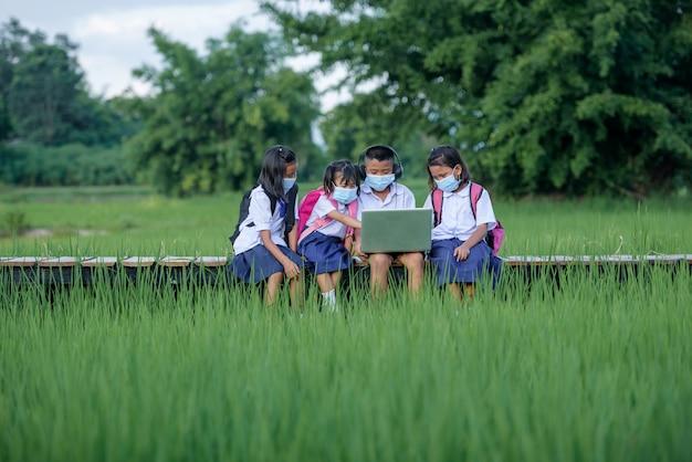 Grundschulkinder mit einer maske unter verwendung des laptops