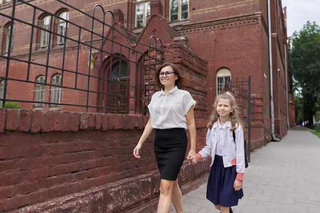 Grundschulmädchen, das mit mutter hand in hand geht, eltern und kind auf dem weg zur schule sprechen. studienbeginn, zurück zur schule