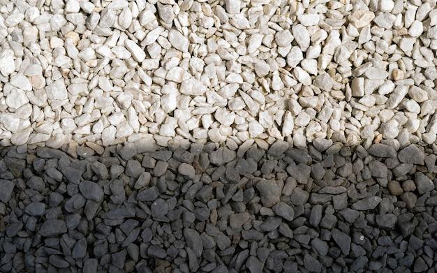 Grundsteingrauer hintergrund vieler kleiner steine auf dem lichtschein. weißer kieselstein auf dem kleinen gartengrund im haus.