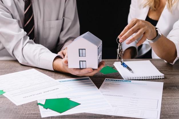 Grundstücksmakler, der dem neuen eigentümer schlüssel gibt