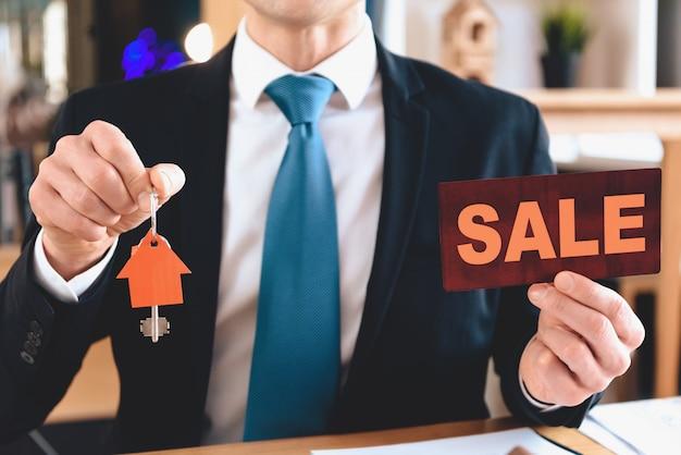Grundstücksmakler hält verkaufszeichen und ausschnittikone des hauses.