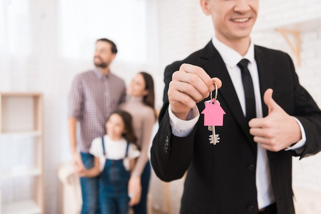 Grundstücksmakler im schwarzen anzug hält schlüssel in form des hauses.