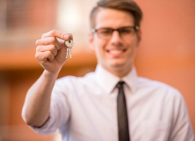 Grundstücksmakler im weißen hemd, das schlüssel zeigt und an der kamera lächelt.