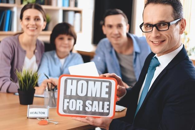 Grundstücksmakler stellt nach hause für verkaufszeichen mit familie dar.