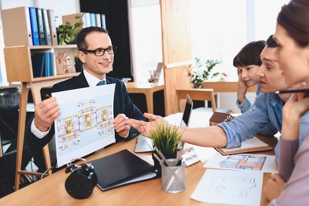Grundstücksmakler zeigt der familie wohnungsplan.