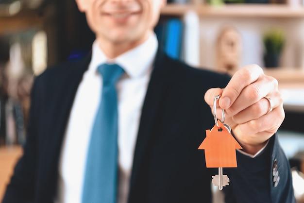 Grundstücksmakler zeigt schlüssel des neuen hauses.