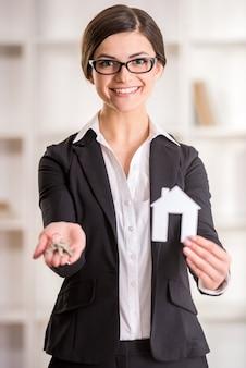 Grundstücksmaklerfrau zeigt nach hause für verkaufszeichen und -schlüssel.