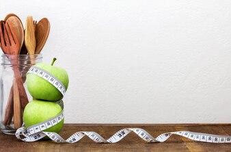 Grüner Apfel mit Maßband auf hölzernem Hintergrund