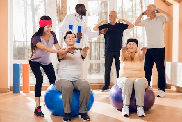 Gruppe ältere menschen, die gymnastik in einem pflegeheim tun.