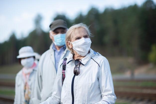 Gruppe älterer senioren mit gesichtsmasken, die zug warten, bevor sie reisen