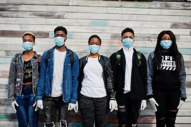 Gruppe afrikanischer teenagerfreunde, die medizinische masken tragen, schützen vor infektionen und krankheiten quarantäne des coronavirus-virus.