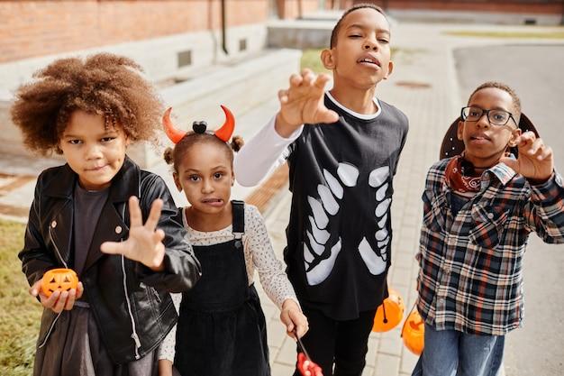 Gruppe afroamerikanischer kinder, die halloween-kostüme tragen und für die kamera posieren, während süßes oder saures ...